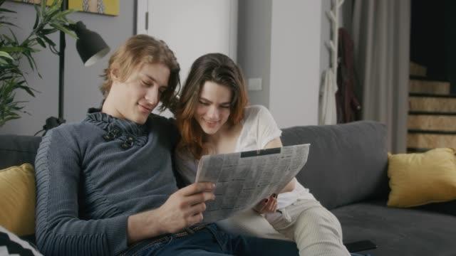 junges paar zu hause - zeitung stock-videos und b-roll-filmmaterial