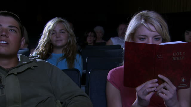 Young couple at movie theater and girl reading book