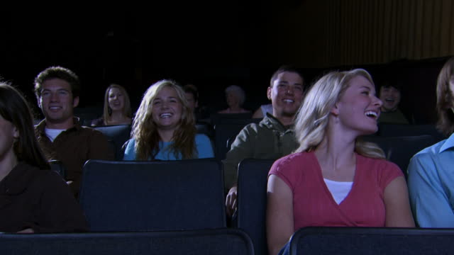 Young couple at movie theater talking with popcorn