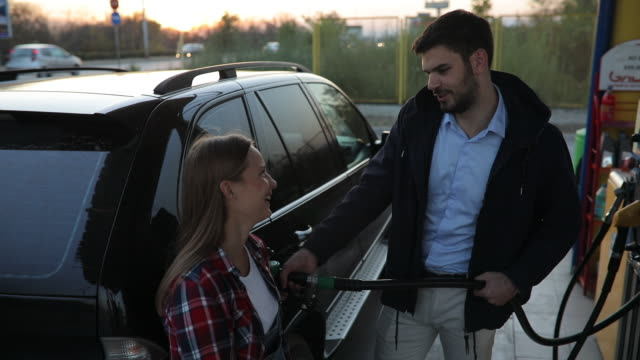 young couple at the gas station - petrol station stock videos & royalty-free footage