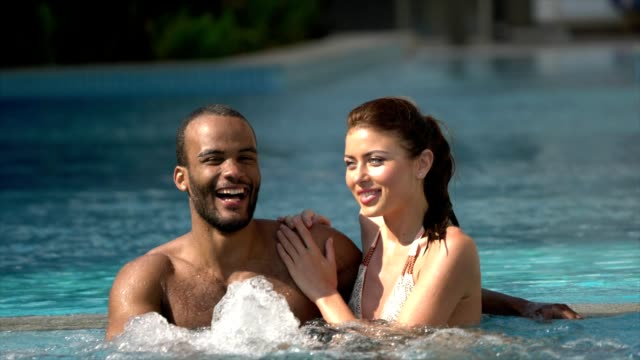 young couple at the swimming pool - tourist resort stock videos & royalty-free footage