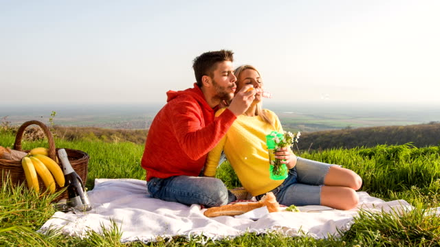 Young couple blowing bubbles during picnic in nature