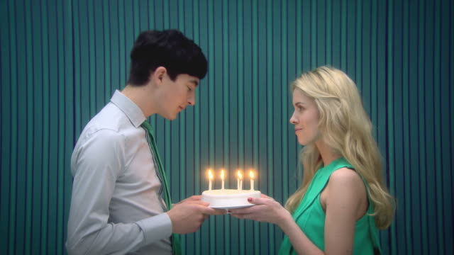Young couple blowing out candles on birthday cake