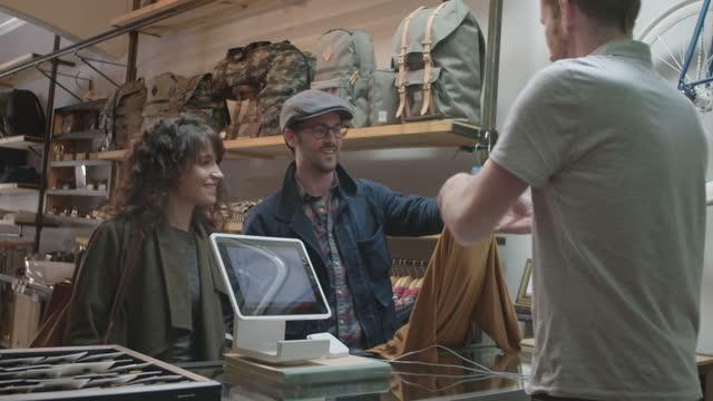 vídeos de stock, filmes e b-roll de young couple brings clothes to checkout counter in hip downtown shop. - geração z
