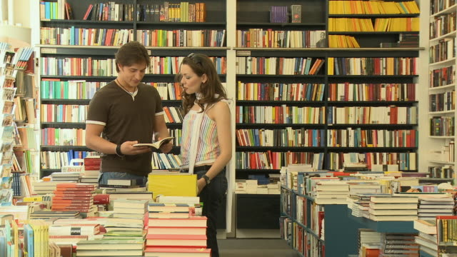 vídeos de stock, filmes e b-roll de zi, ms, young couple browsing book and talking in bookshop, berlin, germany - livraria