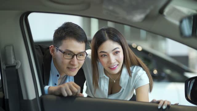 新しい車を買う4k若いカップル - 自動車ショールーム点の映像素材/bロール