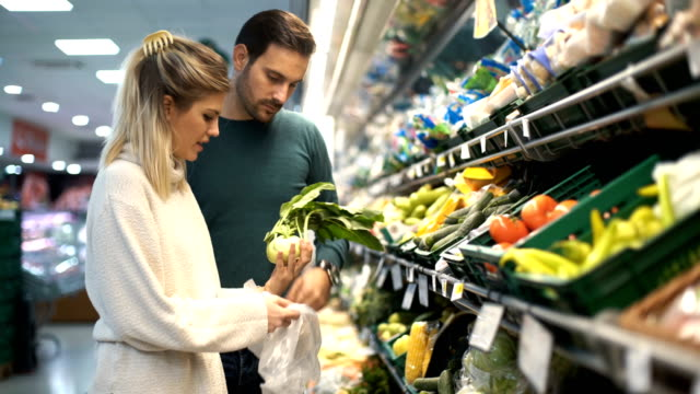 young couple buying groceries at a supermarket. - aisle stock videos & royalty-free footage