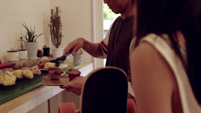 young couple buying muffin. - muffin stock videos and b-roll footage