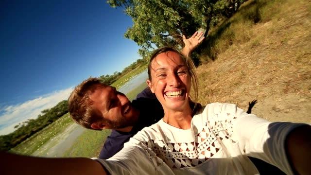 vídeos y material grabado en eventos de stock de pareja joven por el río toma un retrato selfie - posa del loto