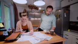 Young couple calculating their domestic budget together in the kitchen, try to safe money, having stresses