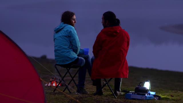 ms young couple camped by side of lake at dusk chatting  - キャンプ用ストーブ点の映像素材/bロール