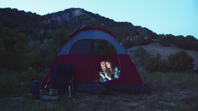 young couple camping in the mountains - equipment点の映像素材/bロール