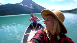 Young couple canoeing on a beautiful lake in Canada, taking selfies