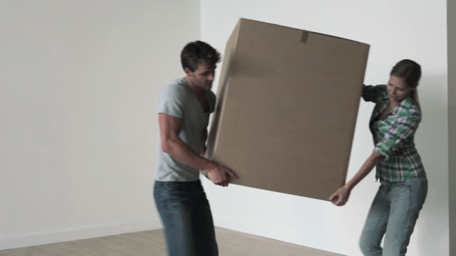 Young couple carrying box into room
