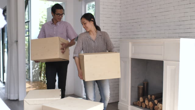 young couple carrying cardboard box into new home - entering stock videos & royalty-free footage