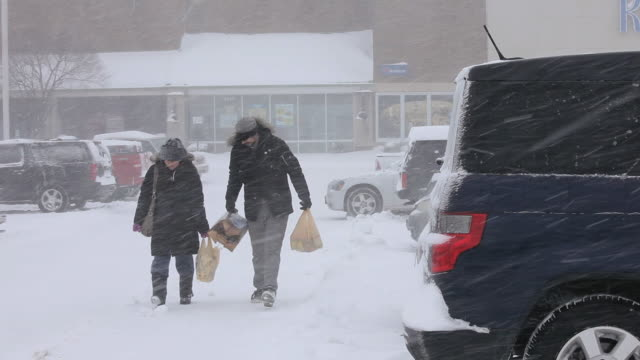 WS Young Couple Carrying Groceries to Car in Snow Storm / Richmond, Virginia, USA