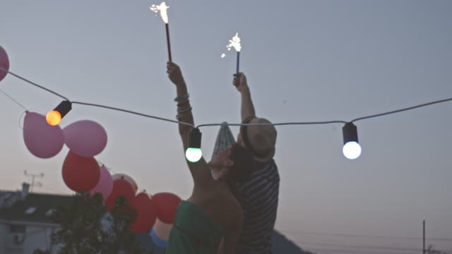 Young couple celebrating with fireworks on rooftop party