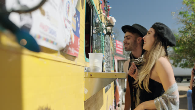 young couple chat with friendly food truck owner and pick up their orders from food truck window. - traditional festival stock videos & royalty-free footage