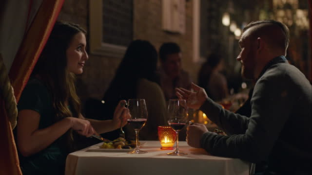 young couple chats over dinner in romantic candlelit restaurant - husband stock videos & royalty-free footage