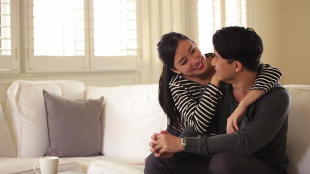 MS Young couple chatting and hugging on sofa at home