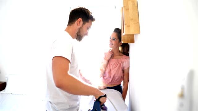 vídeos y material grabado en eventos de stock de pareja joven charlando mientras plancha los paños: preparándose para el concepto de trabajo - plancha