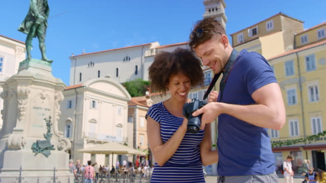 young couple checking the photos they just took with the camera as they stand in the town square - slovenia stock videos & royalty-free footage
