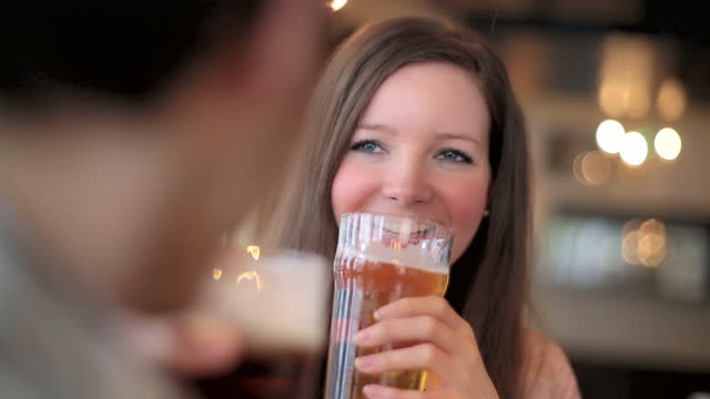 young couple cheers and clink their beer glasses in london pub. - pint glass stock videos & royalty-free footage