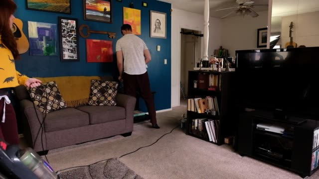 young couple cleans their living room - cleaning equipment stock videos & royalty-free footage
