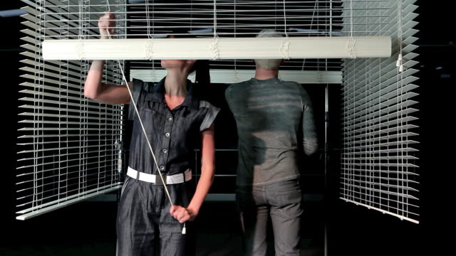 young couple closing venetian blind - jumpsuit stock videos and b-roll footage