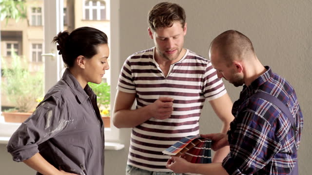 ms young couple consulting house painter about renovating home / berlin, germany - house painter stock videos and b-roll footage