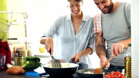 junges paar zu hause kochen. 4k - überbelichtet stock-videos und b-roll-filmmaterial