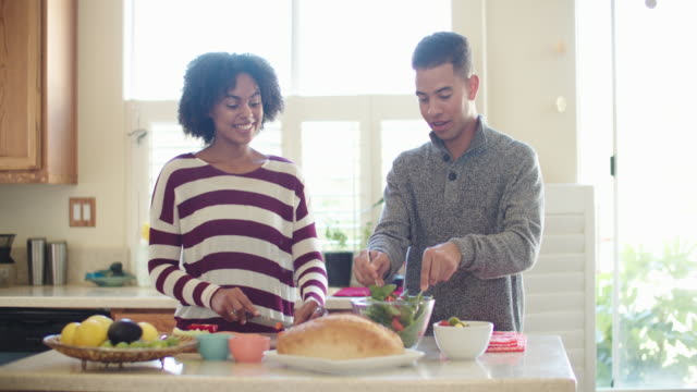 young couple cooking together at home - young couple stock videos & royalty-free footage
