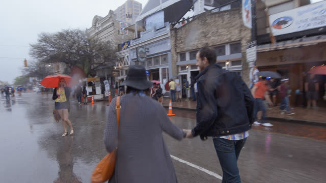 Young couple cross the street in the rain