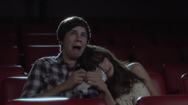 Young couple crying at the movie theater