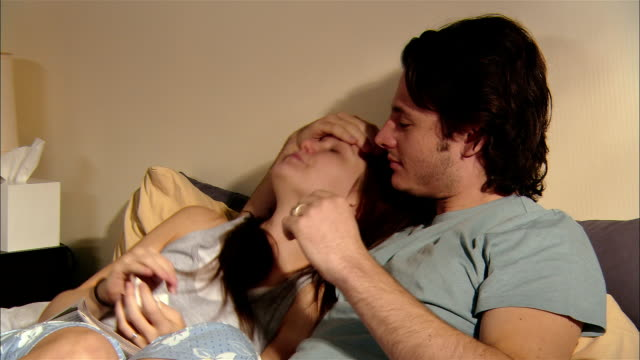 stockvideo's en b-roll-footage met young couple cuddling in bed / she is sick and he takes care of her - verkoudheidsvirus