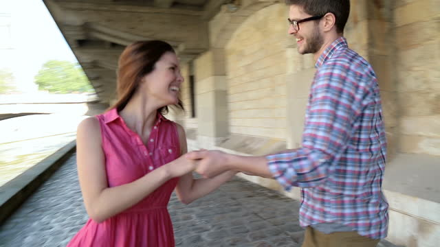 young couple dance and spin in circles by the river seine on sunny day in paris. - cobblestone stock videos & royalty-free footage