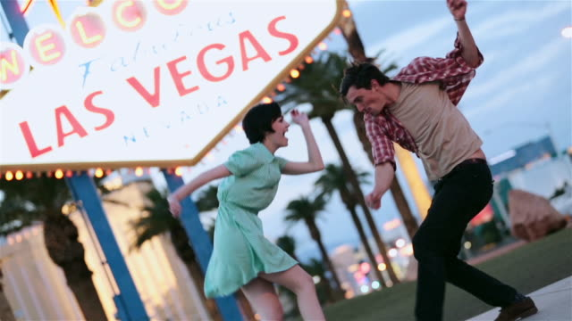 young couple dance wildly in front of famous las vegas welcome sign - twisted stock videos & royalty-free footage