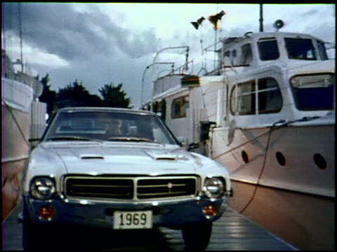 a young couple dances on the dock at sunset her '69 javelin sst is parked between two yachts as the narrator talks about the car the javelin sst is... - wood grain stock videos and b-roll footage