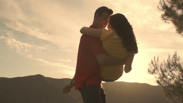 young couple dancing and twirling overlooking mountain in sunset. - slow dancing stock videos and b-roll footage