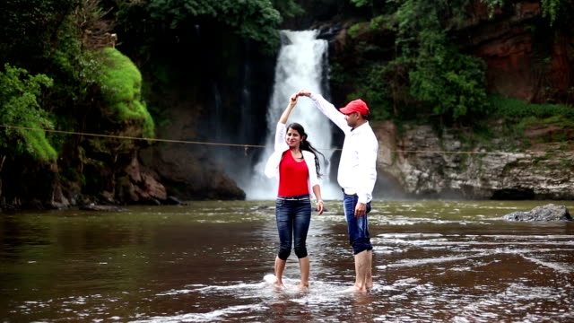 young couple dancing near waterfall - goa stock videos & royalty-free footage
