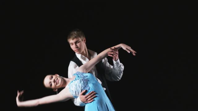 young couple dancing the salsa against a black background - ballroom dancing stock videos & royalty-free footage