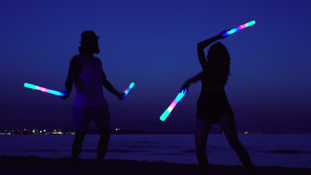 young couple dancing with glowing sticks at night - creatività video stock e b–roll
