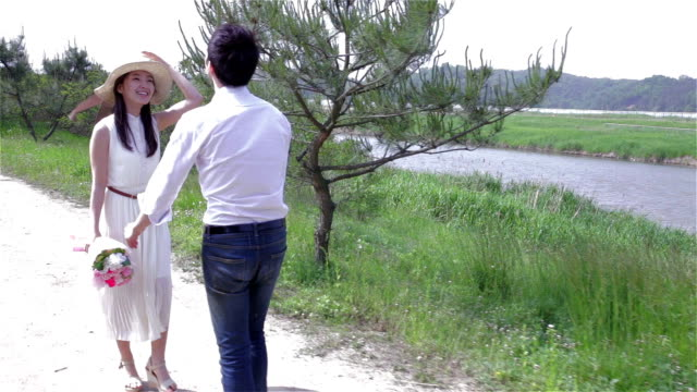 young couple dating at a park with bouquet - korea点の映像素材/bロール