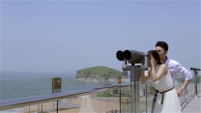 young couple dating at beach and looking seascape through telescope - south korea couple stock videos & royalty-free footage
