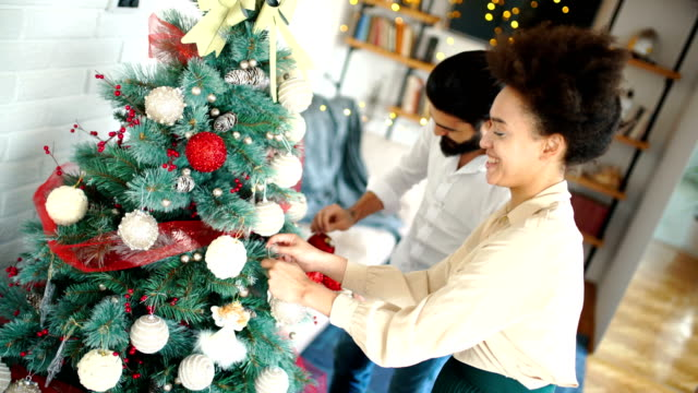 Young couple decorating a Christmas tree.