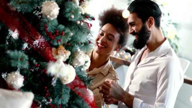 vídeos de stock, filmes e b-roll de casal jovem a decorar uma árvore de natal. - enfeitar a árvore de natal
