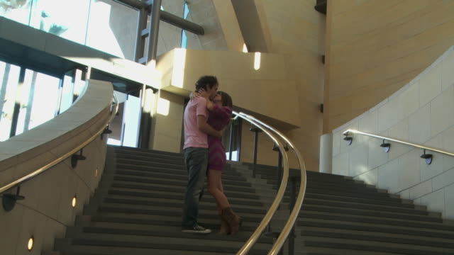 ws, zi, ms, young couple descending steps, embracing and kissing, los angeles, california, usa - gemeinsam gehen stock-videos und b-roll-filmmaterial