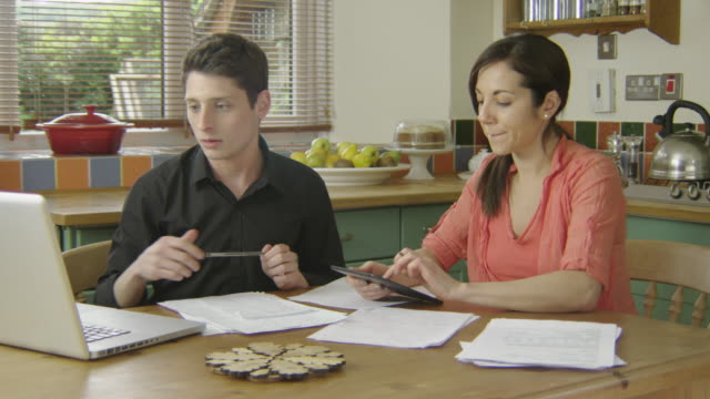 Young couple discussing finance in a country kitchen, looking at laptop and tablet, talking