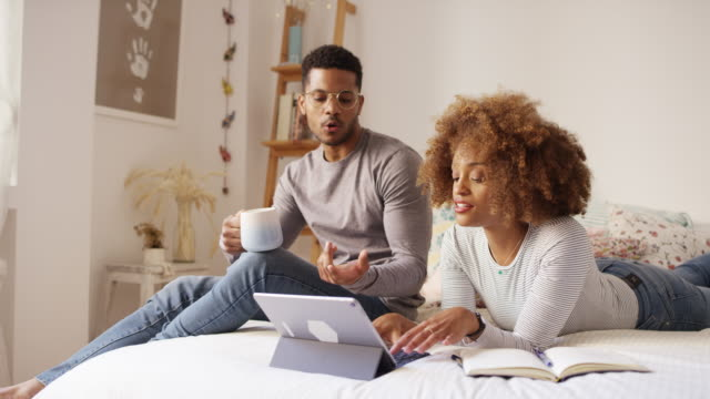 vídeos y material grabado en eventos de stock de pareja joven discutiendo sobre tableta digital en la cama - afro