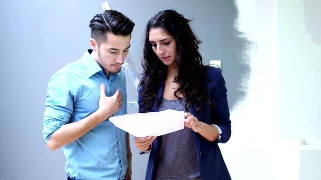 vidéos et rushes de ms jeune couple discute avec les documents - architecte
